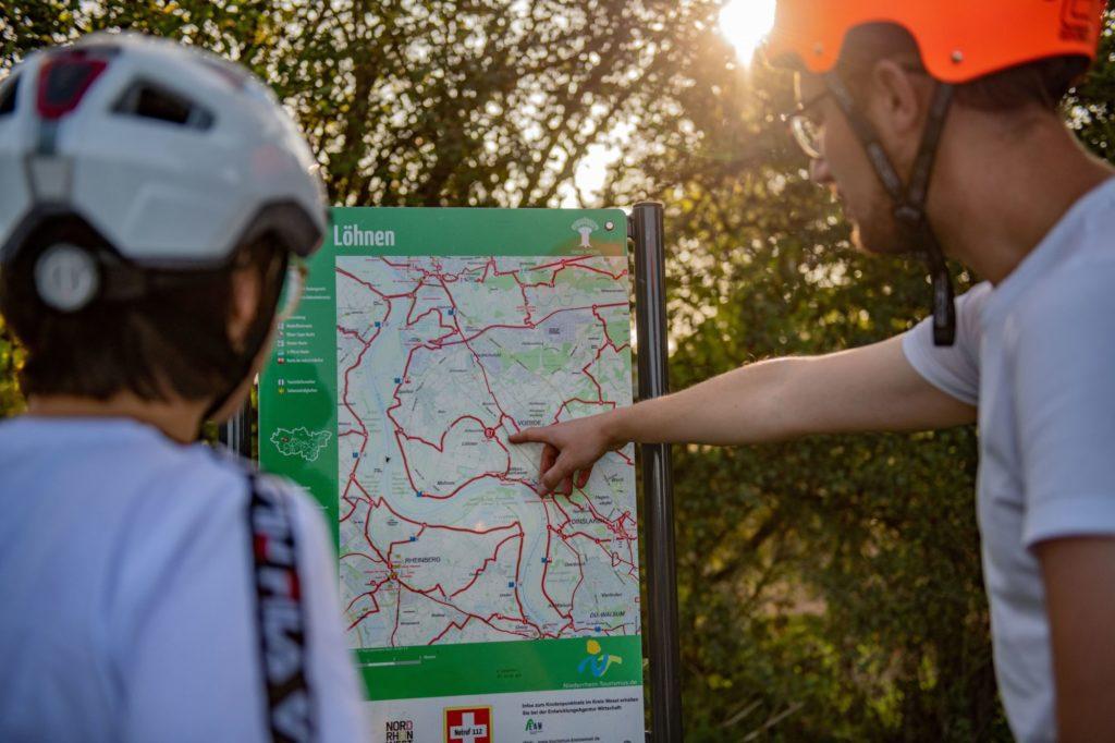 Das Bild zeigt Radfahrer beim betrachten einer Informationstafel zum Radknotenpunktsystem