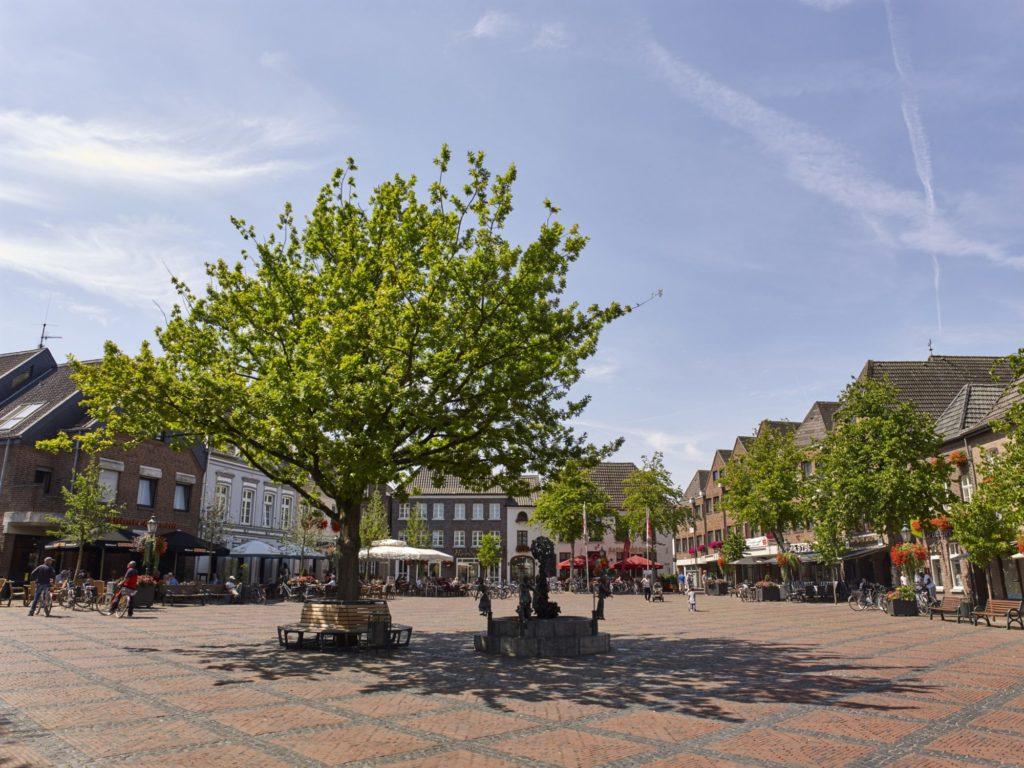 Der Straelener Marktplatz mit großer Eiche und Brunnen.