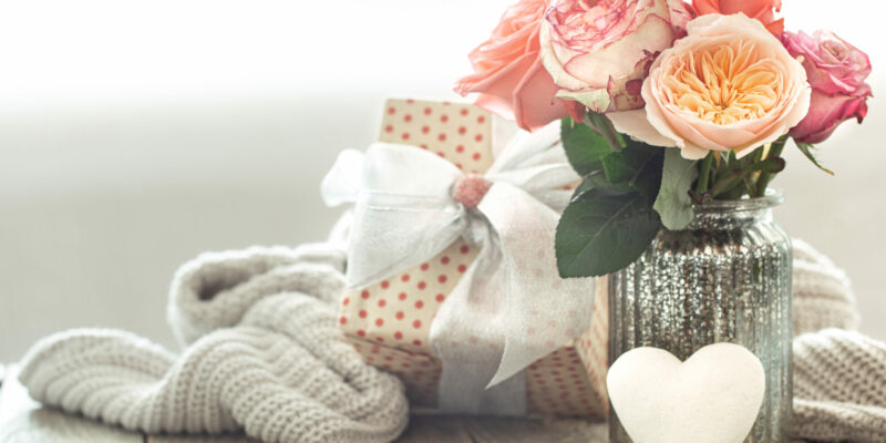 Composition with a bouquet of roses in a glass vase on a blurred light background with a gift box copy space.