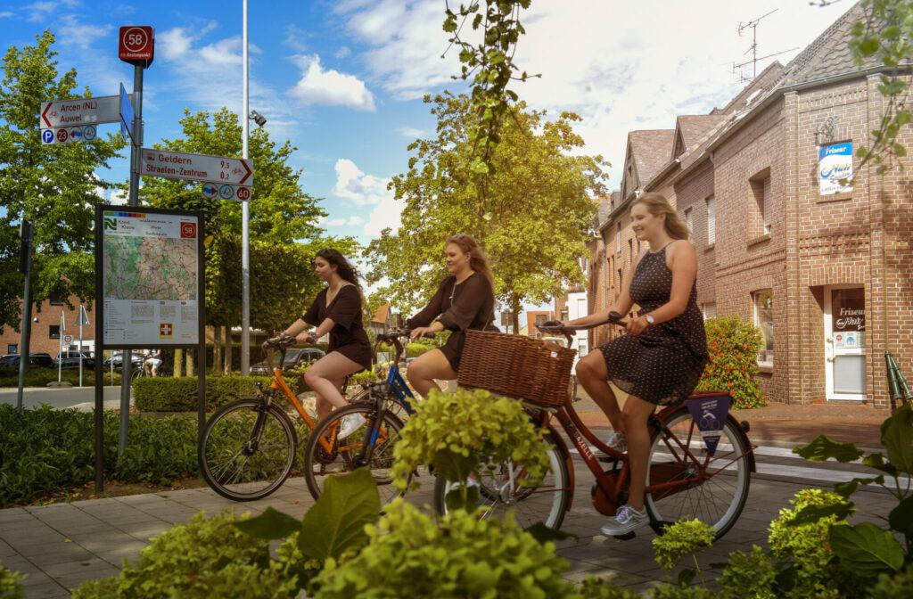 Drei junge Frauen fahren mit dem Rad durch Straelen.